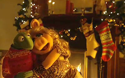 Kermit and Piggy snuggle beside the Christmas tree
